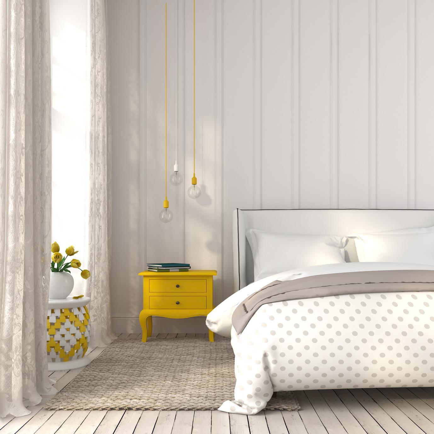 Dormitorio con edredón estampado y plaid gris con cortinas a juego